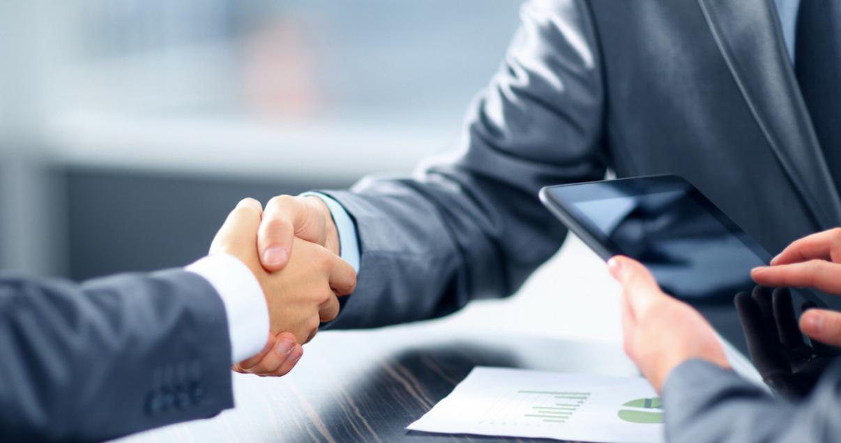Dos brokers inmobiliarios cerrando una transacción inmobiliaria