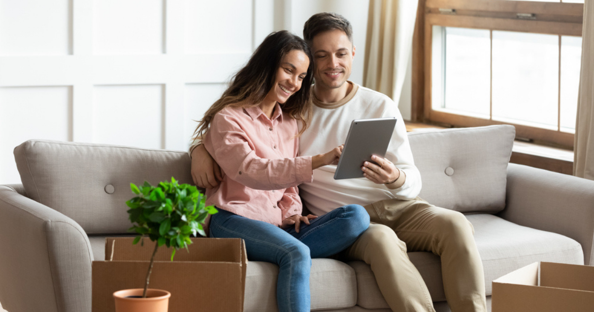Pareja sentados en sofás visualizando propiedades a través de tablet como método de optimizar las ventas con marketing digital