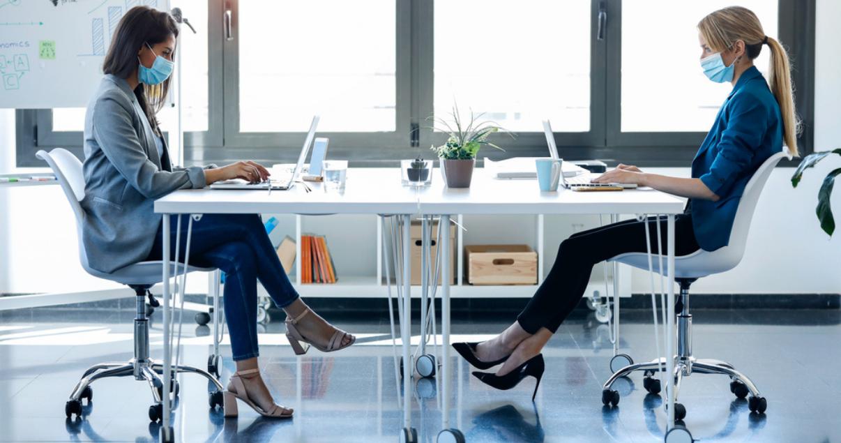 Dos mujeres sentadas en espacio de coworking utilizando las medidas de seguridad en su oficina inmobiliaria post-pandemia