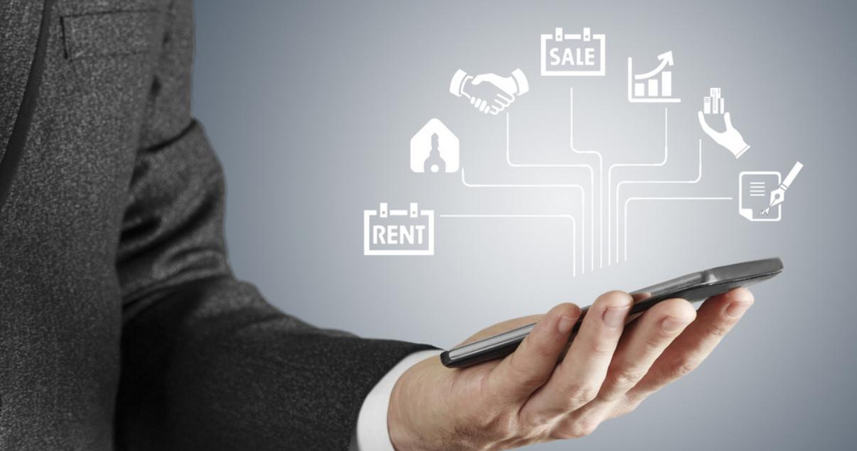 Agente inmobiliario aprovechando de la nueva tecnología inmobiliaria utilizando un CRM desde su dispositivo móvil