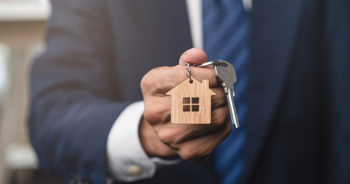 Imagen representativa de un agente entregando su nuevo hogar a cliente gracias a una correcta campaña de email marketing inmobiliario.