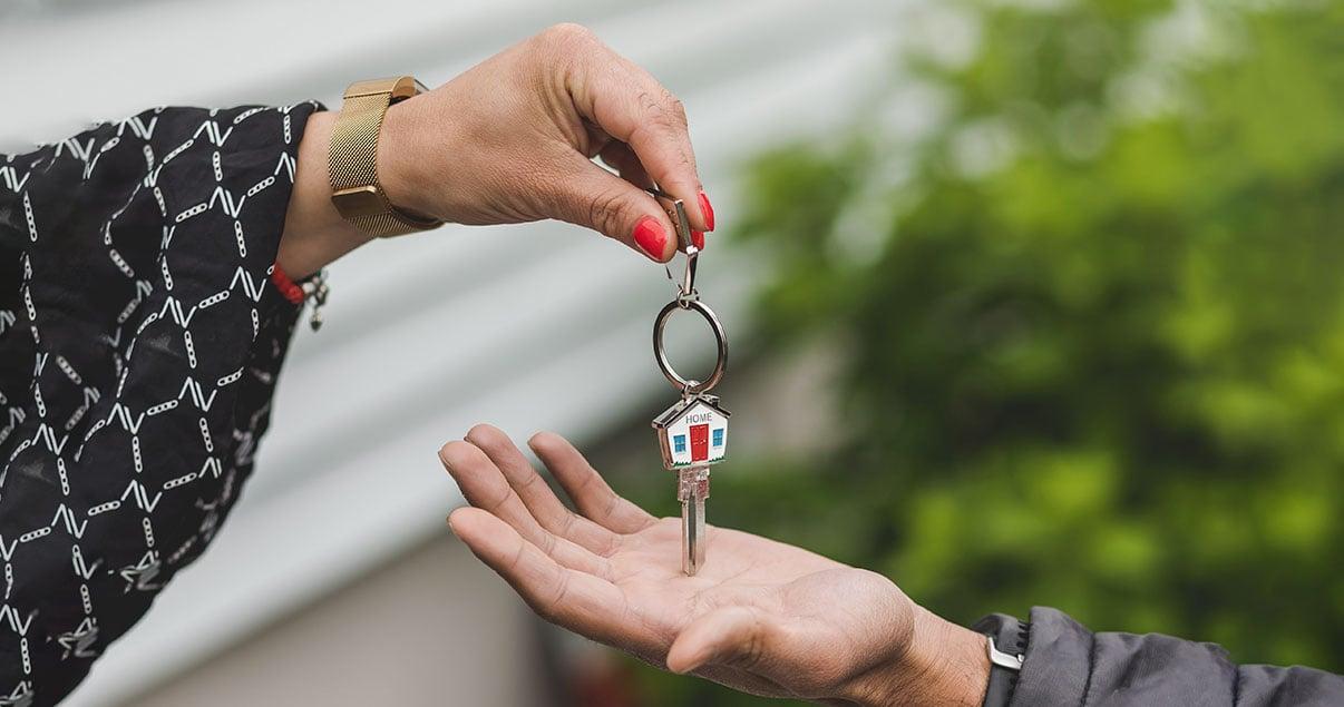Agente inmobiliario entregando llaves de una propiedad