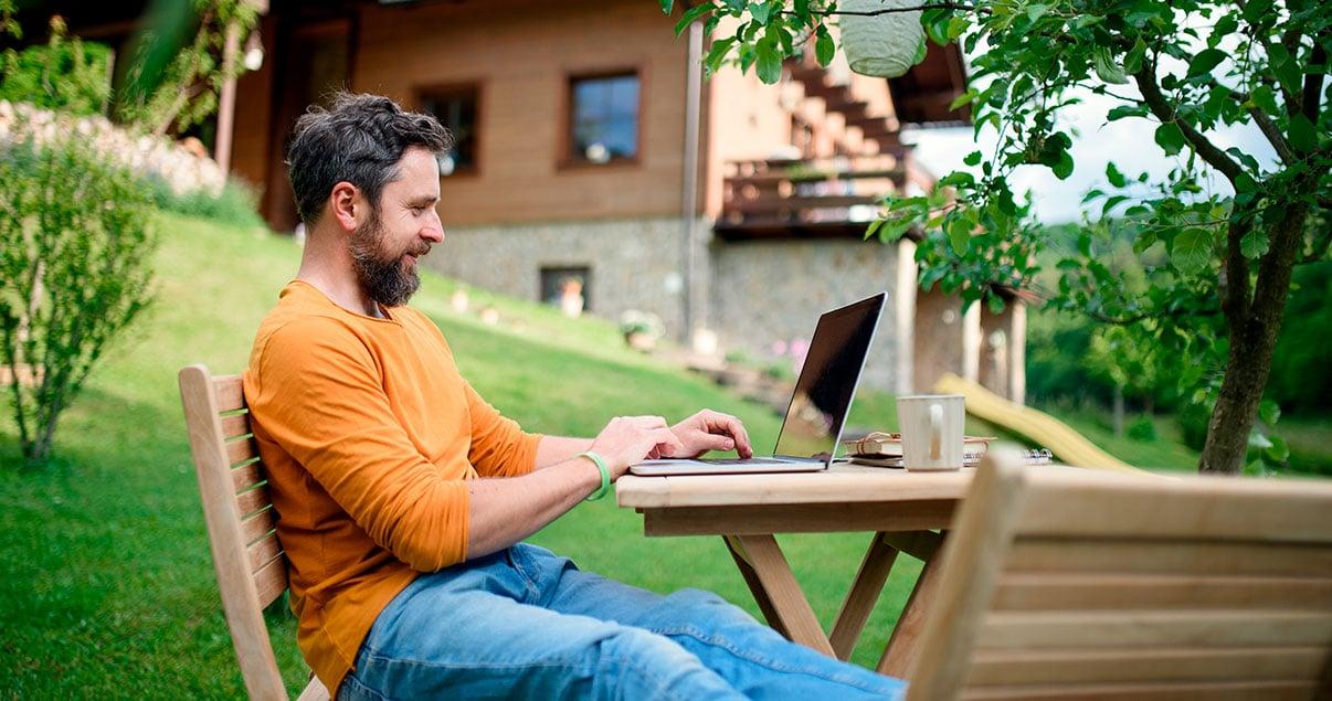 Hombre haciendo homeoffice en un jardín