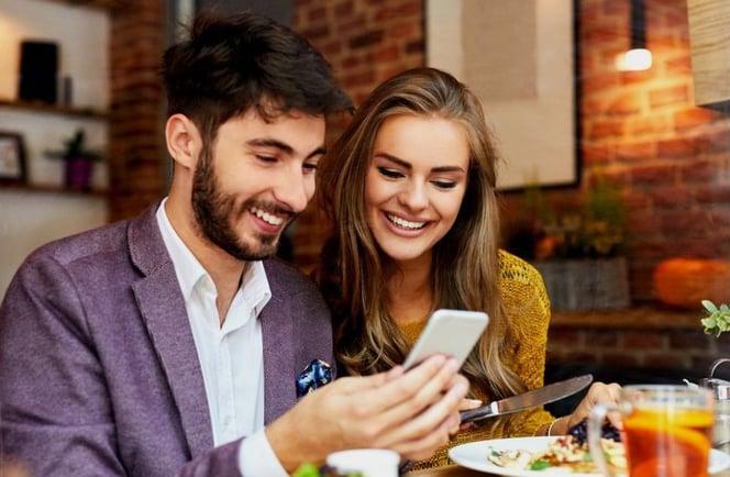 pareja millennial mirando instagram para inmobiliarias en el celular